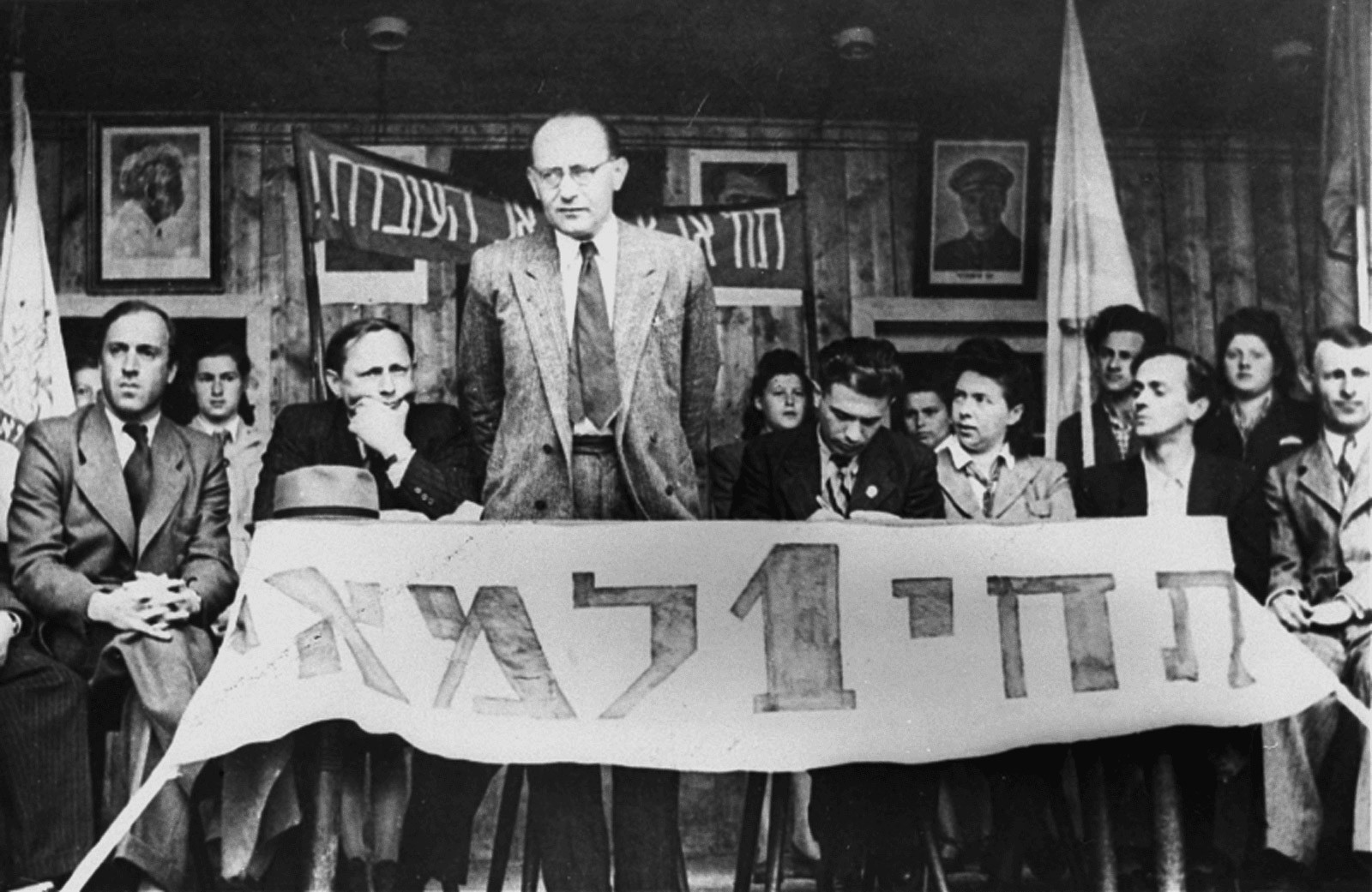 "May 1st, holiday of the working class: Chaim Yahil as emissary of the Jewish Agency with survivors of Nazi persecution (""Displaced Persons"") in the DP Camp of München-Neu-Freimann (1946 / 1948).  The Jewish Agency organized Jewish immigration to Palestine.  Photo: Jack Sutin / United States Holocaust Memorial Museum, courtesy of Saul Sorrin. der NS-Verfolgung (""Displaced Persons"") im DP-Camp München-Neu-Freimann (1946 / 1948). Die Jewish Agency organisierte die Einwanderung nach Palästina.  Foto: Jack Sutin / United States Holocaust Memorial Museum, courtesy of Saul Sorrin"
